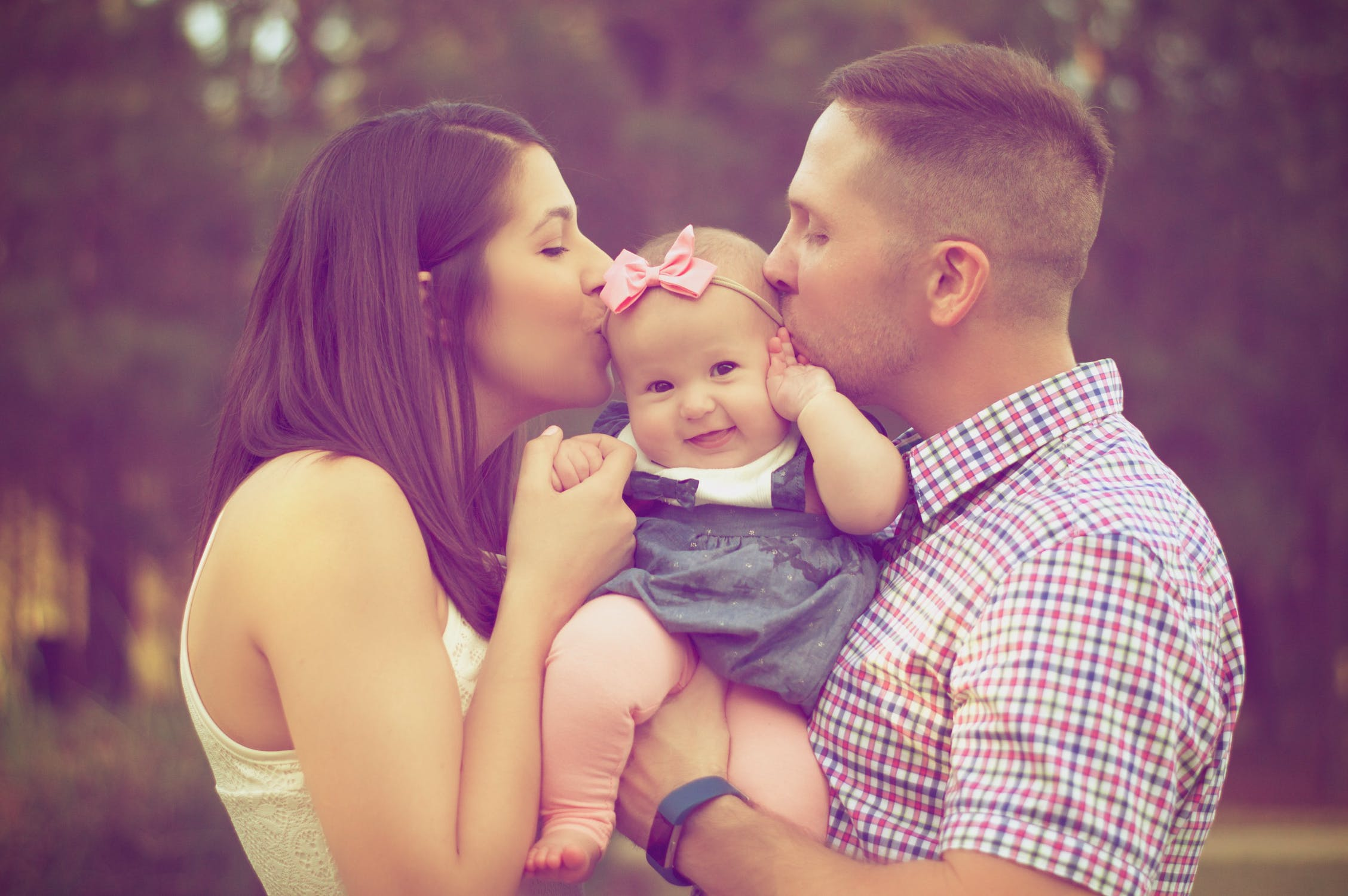 Young couple kissing their baby - how much insurance will keep your family safe? Millennium Brokers